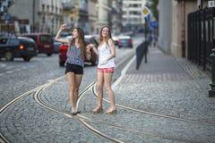 Les filles mignonnes sont amusement dupant autour au milieu des rues de la vieille ville Images libres de droits