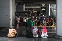 Les filles non identifiées s'asseyant sur l'étape, et les personnes non identifiées attendant un autobus chez le Siam centrent Photos stock