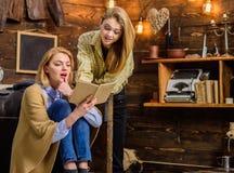 Les filles ont excité au sujet du nouveau roman par l'auteur préféré, concept de littérature Soirée de famille en cottage en bois Image stock