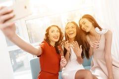 Les filles ont un grand temps à la poule-partie Demoiselles d'honneur et jeune mariée célébrant et faisant le selfie Images libres de droits