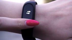 Les filles ont utilisé un bracelet de forme physique La fille vérifie l'impulsion sur le podomètre de bracelet de forme physique  Images libres de droits