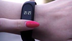 Les filles ont utilisé un bracelet de forme physique La fille vérifie l'impulsion sur le podomètre de bracelet de forme physique  Images stock