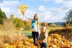 Les filles pilotent un cerf-volant en parc de chute ou d'automne ayant l'amusement Photographie stock libre de droits