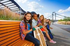 Les filles positives avec des planches à roulettes s'asseyent sur le long banc Image libre de droits