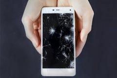 Les filles remet tenir un téléphone avec l'écran cassé Images stock