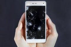 Les filles remet tenir un téléphone avec l'écran cassé Image stock