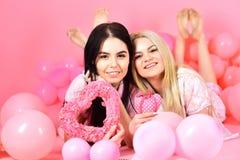Les filles s'étendent près des ballons, jouets de coeur de prises, fond rose Concept de jour de Valentines Blonde et brune sur le Images stock