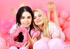 Les filles s'étendent près des ballons, jouets de coeur de prises, fond rose Concept de jour de Valentines Soeurs, amies dans des Image stock