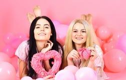 Les filles s'étendent près des ballons, jouets de coeur de prises, fond rose Soeurs, amies dans des pyjamas à la partie de pyjama Photographie stock libre de droits