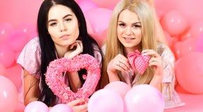Les filles s'étendent près des ballons, jouets de coeur de prises, fond rose Soeurs, amies dans des pyjamas à la partie de pyjama Photos stock