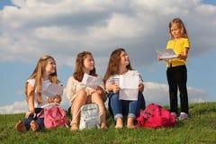 Les filles s'asseyent avec des feuilles et regardent la fille Photos libres de droits