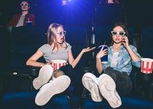 Les filles s'asseyent dans les chaises dans le hall de cinéma La brune parle au téléphone tandis que son ami lui fait la remarque Photo stock