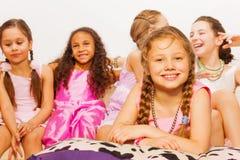 Les filles s'asseyent et s'étendant ensemble sur le lit confortable Photographie stock