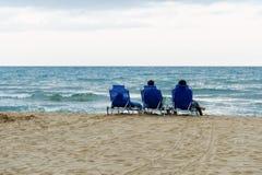 Les filles s'asseyent sur les chaises et le regard de plate-forme à la mer photographie stock