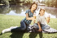 Les filles s'asseyent sur l'eau proche couvrante et la pose Ils tiennent le contre de la crème glacée et regardent sur l'appareil images libres de droits
