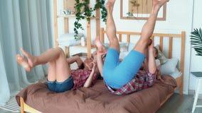 Les filles s'assied sur des épaules de leurs parents et elles tombent sur le lit, mouvement lent banque de vidéos