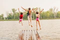 Les filles sautent dans le lac outre du dock Photographie stock libre de droits