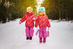 Les filles sautent sur la route neigeuse Photo stock