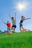 Les filles sautent sur le pré image libre de droits