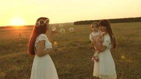 Les filles se r?jouissent et sourient, des bulles volent en parc au coucher du soleil Mouvement lent M?re heureuse jouant avec de clips vidéos