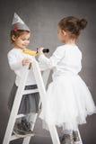 Les filles se tiennent sur une échelle et peignent Photo libre de droits