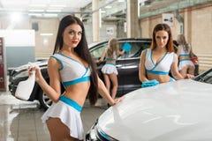 Les filles sexy dans le Formule 1 dénomment la pose à la lave-auto photo stock