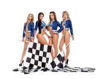 Les filles sexy dans le Formule 1 emballent la veste gardant le drapeau photographie stock libre de droits