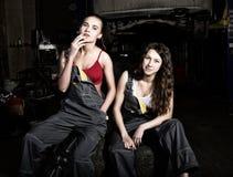 Les filles sexy de mécanique fatiguée s'asseyant sur une pile des pneus sur les réparations d'une voiture, une des filles fument  Photos stock