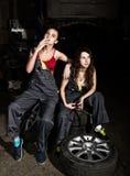 Les filles sexy de mécanique fatiguée s'asseyant sur une pile des pneus sur les réparations d'une voiture, une des filles fument  Photo stock