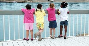 Les filles sur les bateaux de observation d'un dock traversent Photos libres de droits