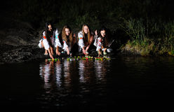 Les filles ukrainiennes dans des chemises ont permis des guirlandes des fleurs sur le wate Photos stock