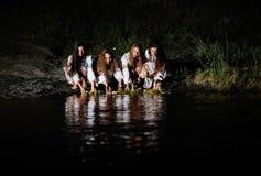 Les filles ukrainiennes dans des chemises ont permis des guirlandes des fleurs sur le wate Photo stock