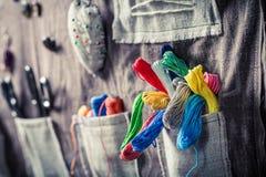 Les fils, les boutons et les ciseaux colorés dans le tapis travaillent Photographie stock libre de droits