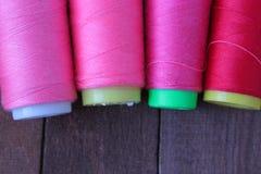 Les fils de couture colorés se trouvent sur la table en bois brune Images libres de droits