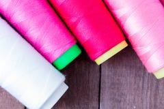 Les fils de couture colorés se trouvent sur la table en bois brune Photo stock