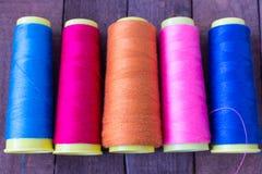 Les fils de couture colorés se trouvent sur la table en bois brune Images stock