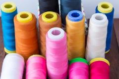 Les fils de couture multicolores se tiennent sur une table en bois Photos libres de droits