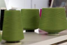 Les fils de vert dans les cônes sont sur la machine à tricoter Images stock