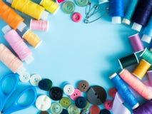 Les fils et les boutons de couture multicolores sur le fond bleu avec la copie espacent la configuration d'appartement Photographie stock
