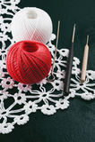 Les fils irisent, les crochets de crochet, serviette tricotée sur un fond bleu Image stock