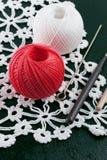 Les fils irisent, les crochets de crochet, serviette tricotée sur un fond bleu Image libre de droits