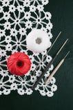 Les fils irisent, les crochets de crochet, serviette tricotée sur un fond bleu Photo libre de droits
