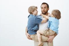 Les fils tirent profit du père aimant et de soin Portrait du papa européen drôle naïf tenant des enfants sur des mains images stock