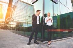 Les financiers qualifiés gais d'homme et de femme parle pendant la coupure au travail image stock