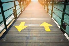 Les flèches jaunes bi-directionnelles du trafic signent l'indication la direction deux sur le pont en bois photographie stock libre de droits