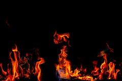 Les flammes du feu sur la texture noire de fond d'art abstrait, les étincelles d'un rouge ardent brûlantes se lèvent du grand feu image libre de droits