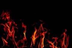 Les flammes du feu sur la texture noire de fond d'art abstrait, les étincelles d'un rouge ardent brûlantes se lèvent du grand feu image stock