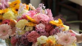 Les fleuristes décorent la salle avec des fleurs banque de vidéos