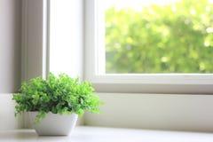 Les fleurs artificielles décoratives s'approchent de la lumière de fenêtre Photographie stock libre de droits