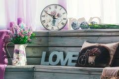 Les fleurs dans un vase avec le mot aiment avec un oreiller avec une photo d'une bicyclette sur le fond des conseils en bois Image libre de droits